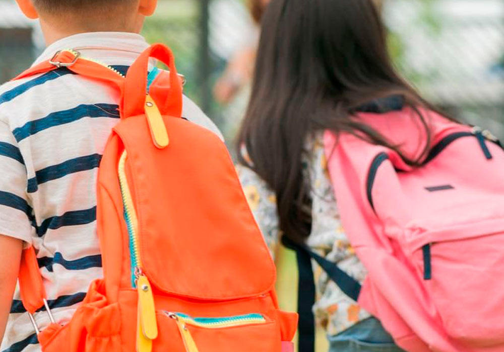 two children with bright pink and orange backpacks
